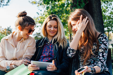 Three smiling girls talking and using smart devices