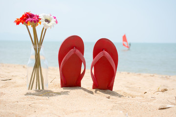 Red old slippers and flower on the beach with windsurf backgroun