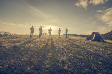 Group Of People relaxing on field with sunrise