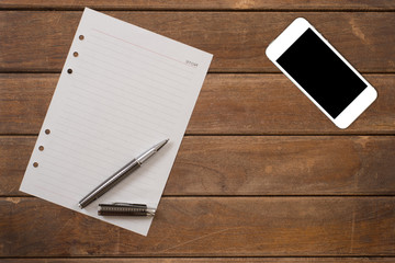 Notepad with pen and smart phone on office wooden table.