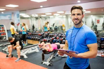 Handsome trainer using tablet in weights room