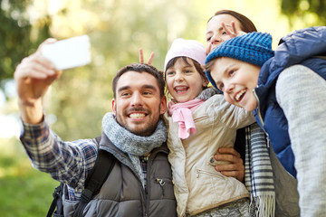 family taking selfie with smartphone outdoors