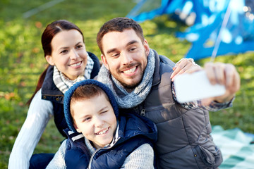 family with smartphone taking selfie at campsite