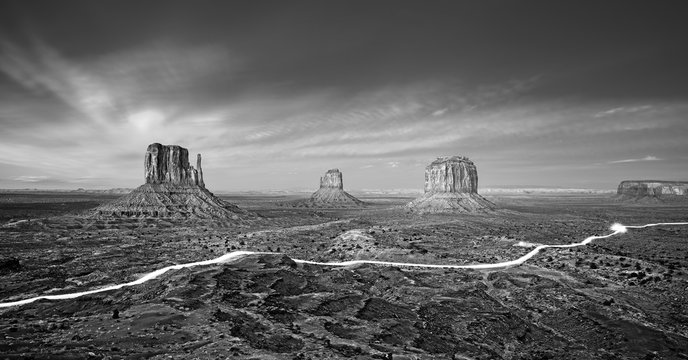 Black and white photo of Monument Valley with car lights trails at night, USA.