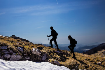 silhouettes of hikers walking in the mountains breathing clean a