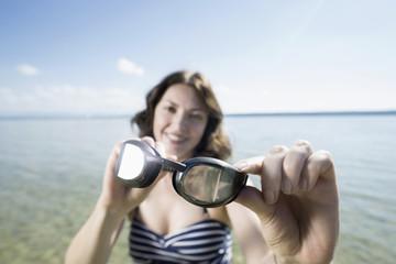 Mature woman holding swimming goggles and smiling at lake, Bavaria, Germany