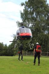 Hubschrauber wird von einem Flughelfer am Landeplatz eingewiesen