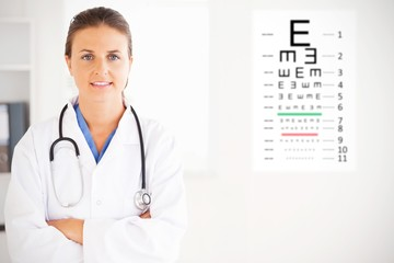Composite image of charming doctor with arms crossed