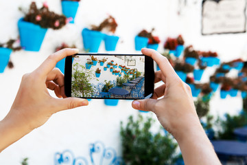 Female hands taking a picture with mobile phone in a white village in Andalusia, Spain.