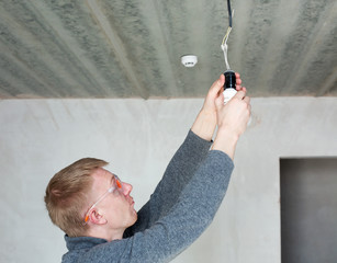 A man in safety glasses changing energy saving light bulbs