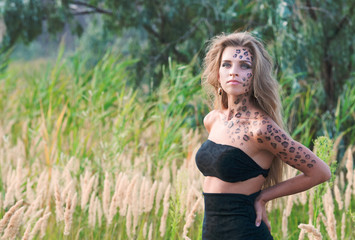 Outdoors portrait of a pretty blond woman in wild cat makeup and bodyart
