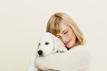Woman hugging puppy in white studio