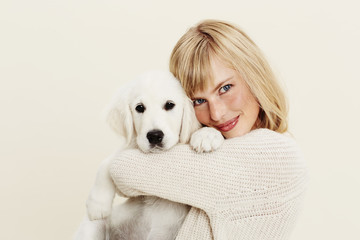 Blond woman hugging puppy in studio, portrait