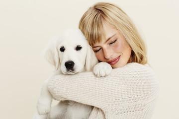 Beautiful woman hugging puppy, close up