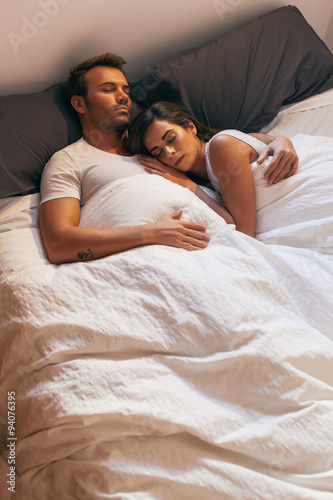Young Couple Sleeping In Bed With Morning Light