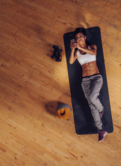 Fitness woman lying on mat using mobile phone