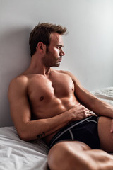 Sexy Man Sitted on a Bed