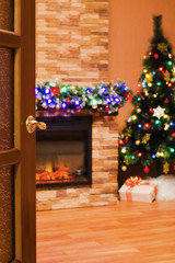 room with an electric fireplace and a Christmas tree