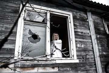 Woman staying near the broken window