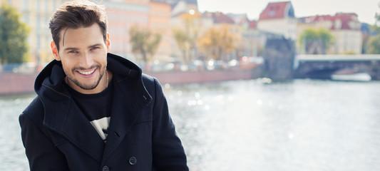Paronamic photo with handsome smiling man in coat - fototapety na wymiar