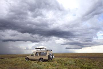 Safari car in the Serengeti Mara savanna before thunderstorm in the rainy season