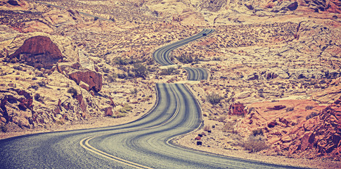 Vintage toned curved desert highway, travel adventure concept.