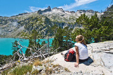 Girl hiker enjoying the Aubert lake and Neouvielle peak landscap