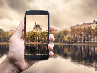 Photographing with smartphone in hand. Travel concept. Moscow cityscape, Patriarch Ponds
