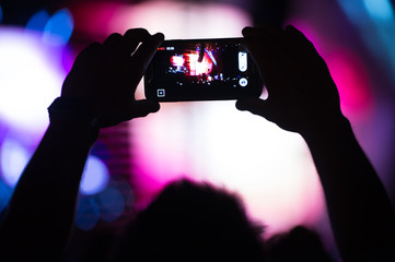 Boy makes photo with his smartphone to a concert to share the moment with friends on social networks, image with blurred and faded effect with grain