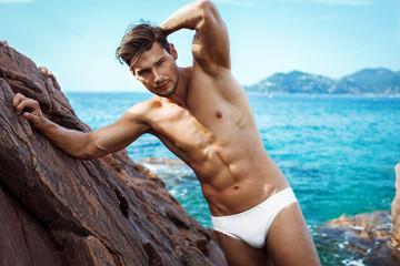 Sexy man in underwear posing on sea scenery