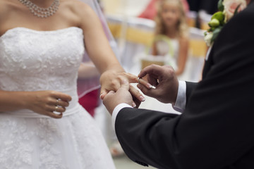 Groom slipping ring on finger of bride at wedding