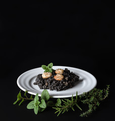 Black risotto and herbs