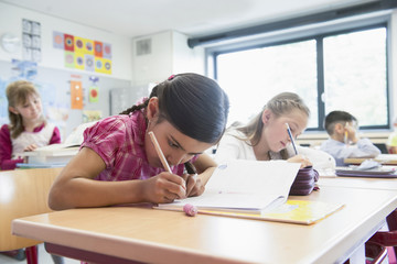 School students writing notebooks in classroom, Munich, Bavaria, Germany