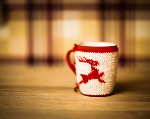 insulated wool cloth mug with embroidered deer on the wooden table