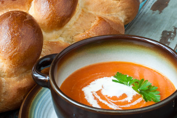 Bowl of home made pumpkin soup topped with a little cream and fresh parsley. Served on a rustic wooden table with freshly baked crusty bread.