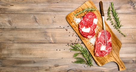 Raw beef meat Rib Eye Steak with herbs and spices
