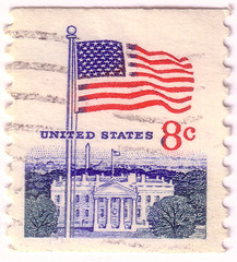 A postage stamp printed in the United States, features waving US flag, circa 1968