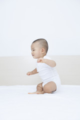 Fototapeta Cute Chinese baby boy playing in bed