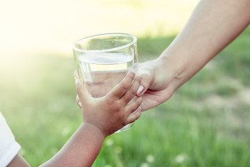 Woman hand giving glass of fresh water to child in the park