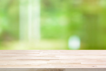 Wood table top on blur abstract green background