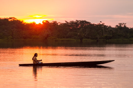 ecuador amazon people tribe indigenous biodiversity canoe boat cuyabeno amazonia indigens mature male with canoe on laguna grande cuyabeno national park ecuador at sunset ecuador amazon people tribe