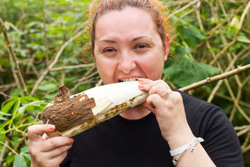 Plump Woman Chewing A Cassava Root