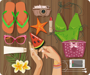 Workplace concept. Top view with textured table, swimsuit, starfish, camera, slippers, cosmetic, phone, headphones, sunglasses, sun cream, candy, lollipop, flowers