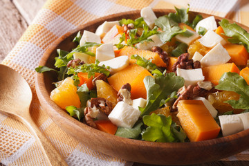 Healthy salad with persimmon, arugula and cheese close-up