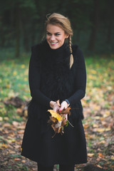 Blonde young woman holding autumn leaves