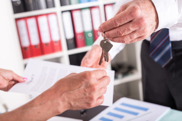 Realtor giving house keys to his client