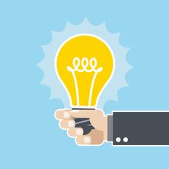 Innovative idea - shining light bulb in hand