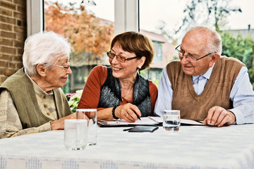 Elderly couple and daughter, making plans