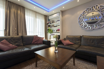 Modern living room interior with blue ceiling lights