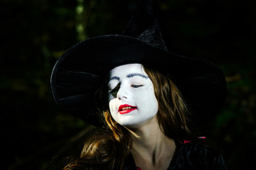 Girl in the forest dressed Halloween witch costume